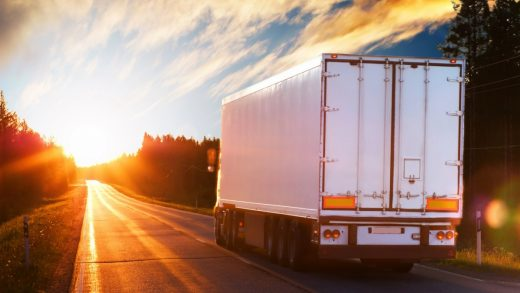 Truck on road as sunrises