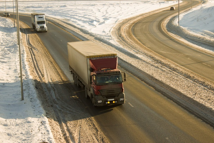 Trucks on snowy winter highway road