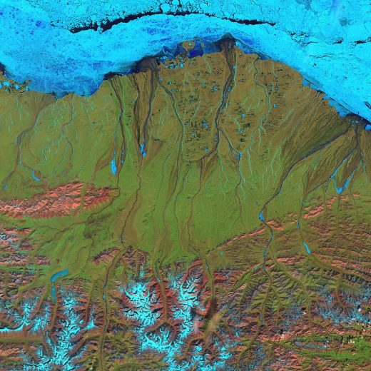 Landsat 7 false-color image of the North Slope. Along the coast, fast ice still clings to the shore in a solid, frozen sheet. At the top of the scene is the drifting sea ice. A dark blue strip of open water, known as a flaw lead, separates the fast ice from the drifting sea ice. The Brooks Range is visible at the bottom. (June 2001)