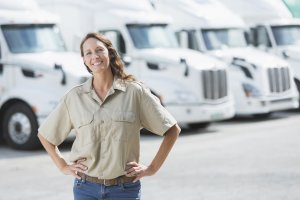 The trucking industry is also trying to recruit more women, who currently make up a small fraction of the workforce., Woman standing in front of semi-trucks