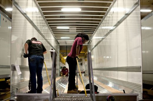 Workers drill holes to secure flooring to the frame of a semi trailer at the Wabash National Corp. facility in Lafayette Indiana
