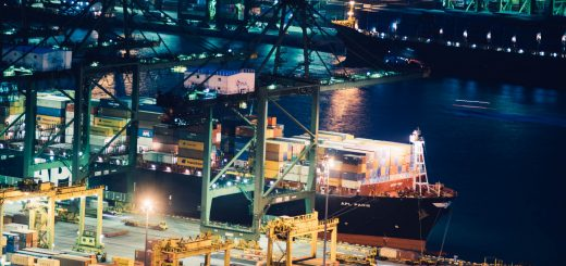 Photo of port with cargo ship picking up and offloading cargo