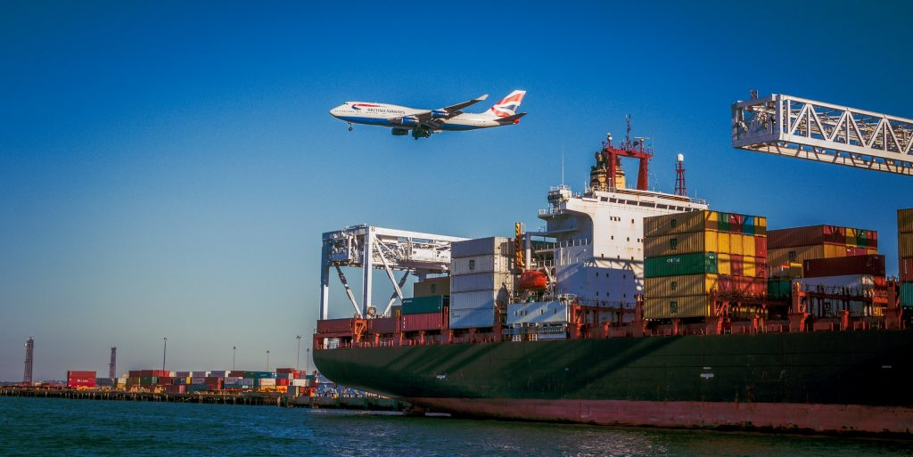 British Airlines Plane flying over Cargo Ship at Port