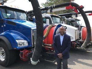 Archie Ferguson, City of Kirkland fleet manager, is shown with the city's three Kenworth T880s, City Using Vacuum Trucks for Flooding